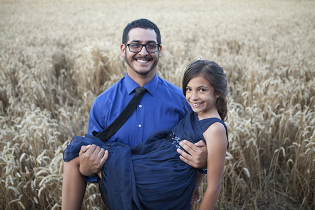 Wedding guest holding young bridesmaid in his arms with field of wheat in the background