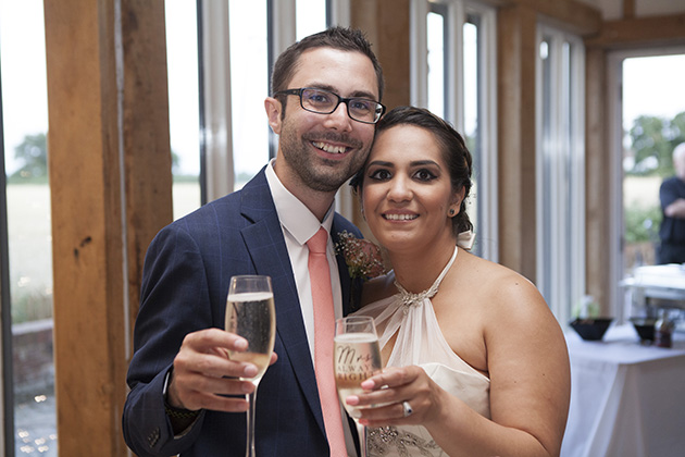 Bride and groom holding out glasses of champagne and looking at camera
