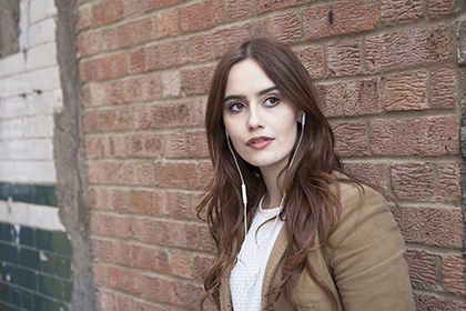 Portrait of young woman leaning against old brick wall listening to music on headphones