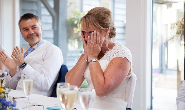 Emotional bride with hands on her face during wedding speeches