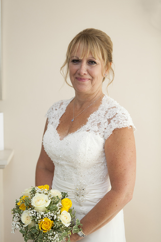 Portrait of bride at home holding bouquet of white and yellow flowers