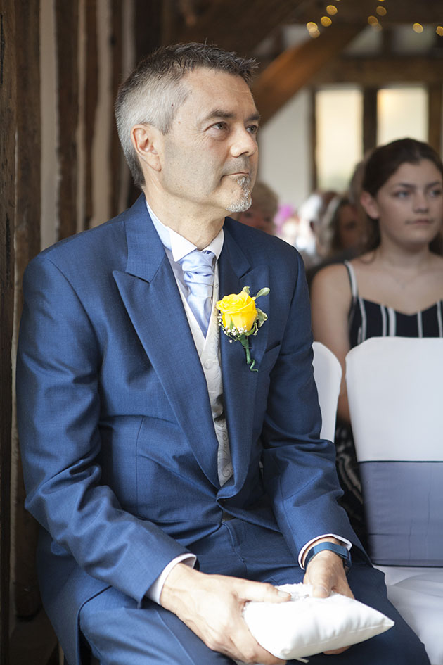 Best man sitting at wedding ceremony holding rings on a cushion