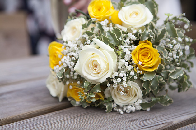 Yellow and white bouquet of wedding flowers on wooden table