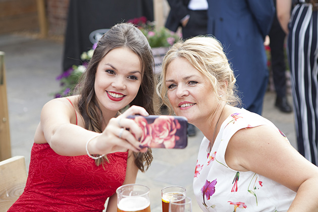 Two female wedding guests taking a selfie