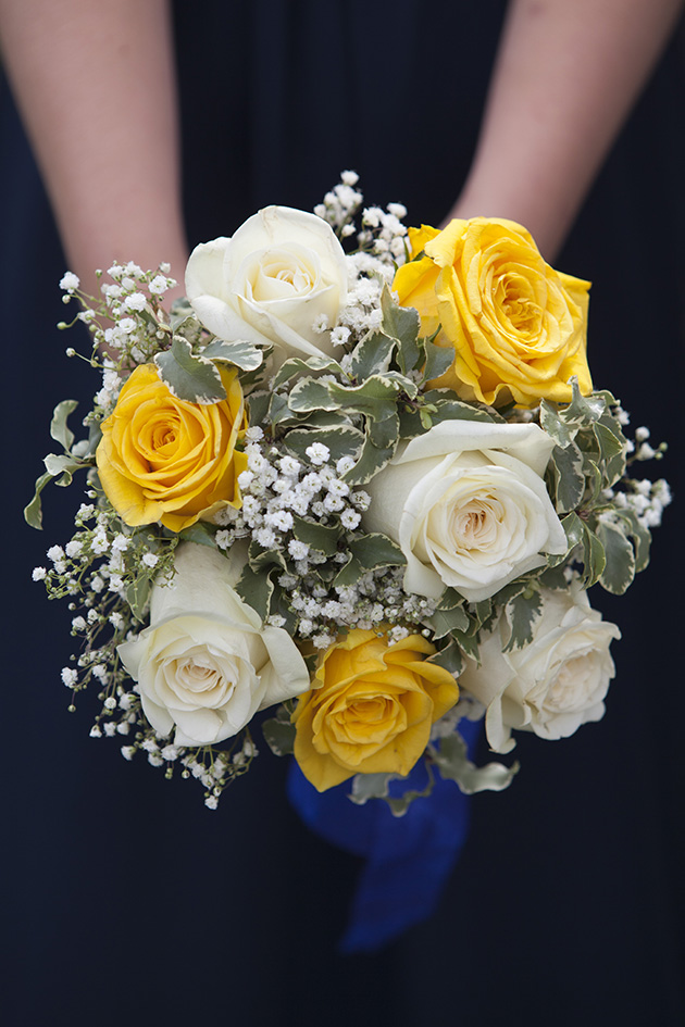 Hands held out holding a bouquet of yellow and white flowers