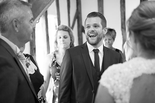 Wedding guest in receiving line looking at groom and laughing