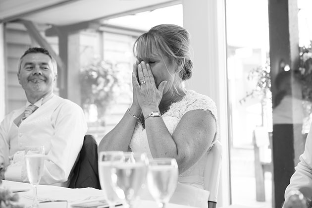 Emotional bride at top table during wedding speeches