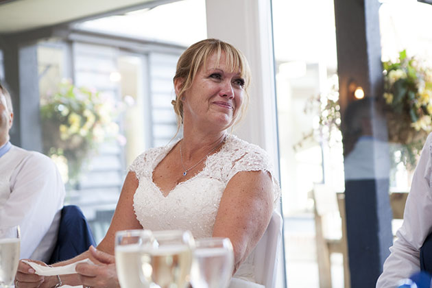 Emotional bride at top table during wedding speeches looking to the side