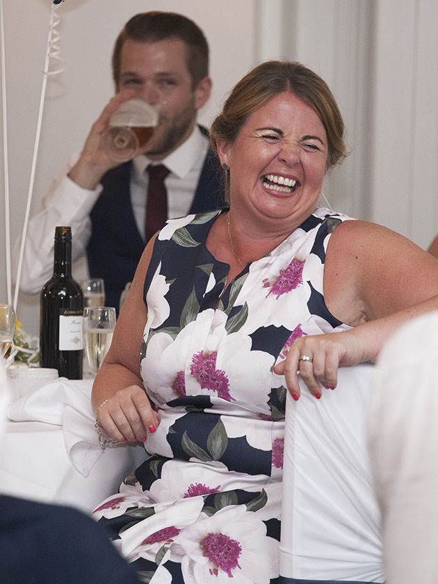 Wedding guest laughing during wedding speeches