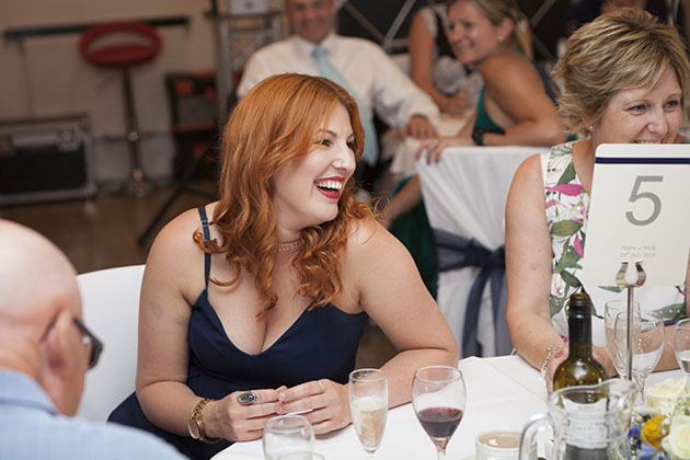 Wedding guest laughing at a table